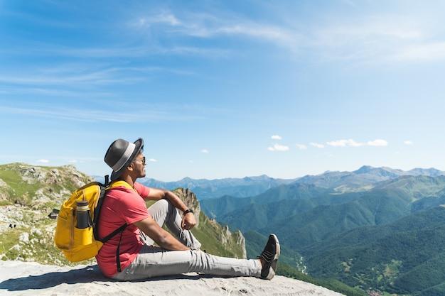 Jovem, apreciando as vistas no topo da montanha