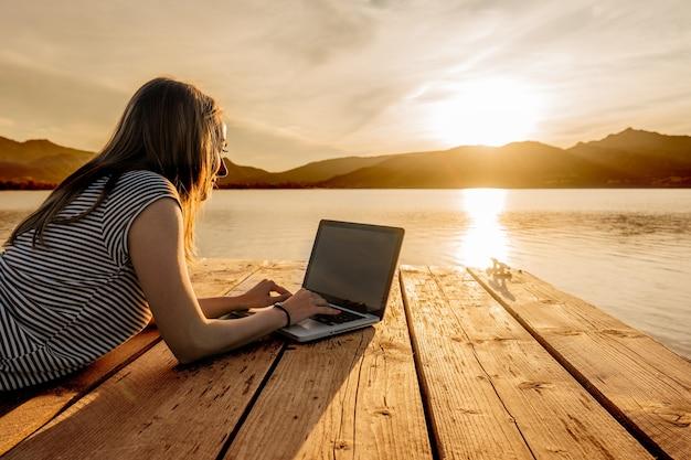 Jovem apreciando sua criatividade, escrevendo o livro em um píer ao pôr do sol. nova oportunidade de trabalho