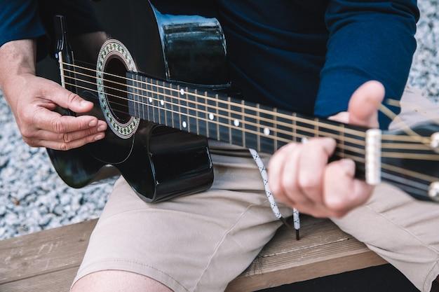 Jovem aprende a tocar violão nas ruas da cidade. estilo de vida. foto de alta qualidade