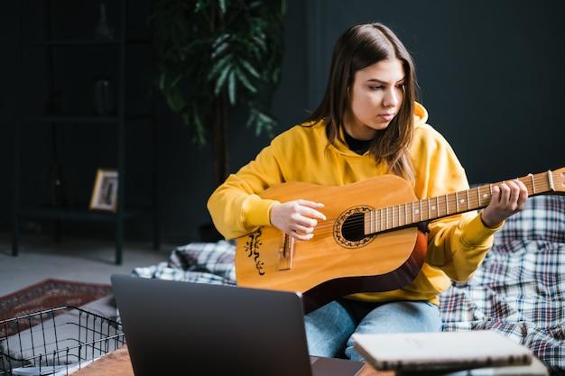 Jovem aprendendo a tocar violão em casa, assistindo a cursos on-line usando um laptop, sentada na cama