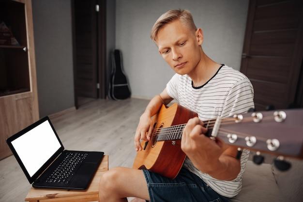 Jovem aprendendo a tocar violão em casa
