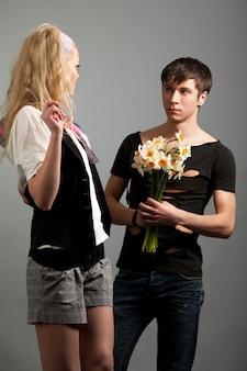 Jovem apresentando buquê de flores para uma linda mulher loira sobre fundo gey no estúdio fotográfico. conceito de estilo de vida de moda e beleza