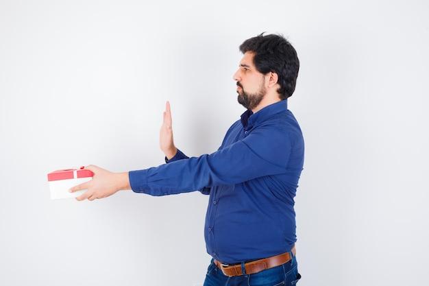 Jovem apresentando caixa de presente e mostrando o sinal de pare em jeans e camisa azul e olhando com medo, vista frontal.