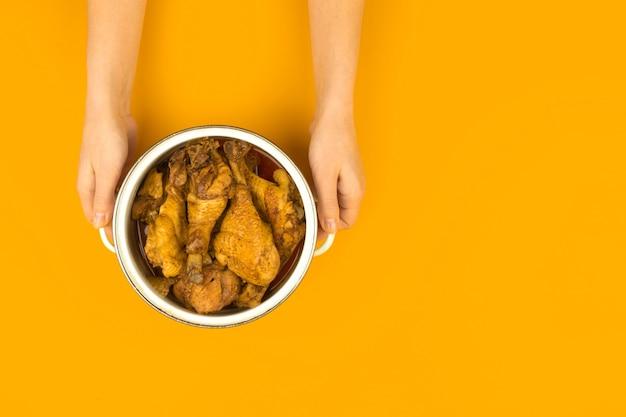 Jovem apresentando frango frito em uma panela em um plano de fundo colorido plano, conceito de cozinha laranja, vista de cima e foto do espaço de cópia