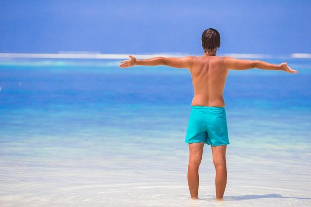 Jovem, aproveitando as férias de verão na praia tropical