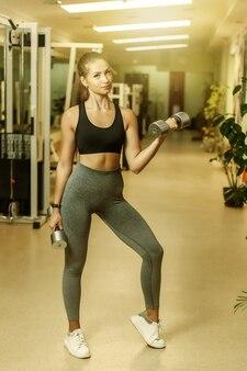 Jovem apta a fazer elevador para o bíceps com halteres na sala de ginástica. conceito de estilo de vida saudável