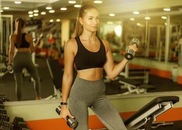 Jovem apta a fazer elevador para o bíceps com halteres no ginásio. conceito de estilo de vida saudável