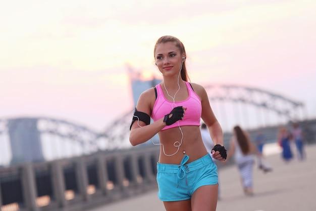 Jovem apta a mulher em roupas esportivas ao ar livre