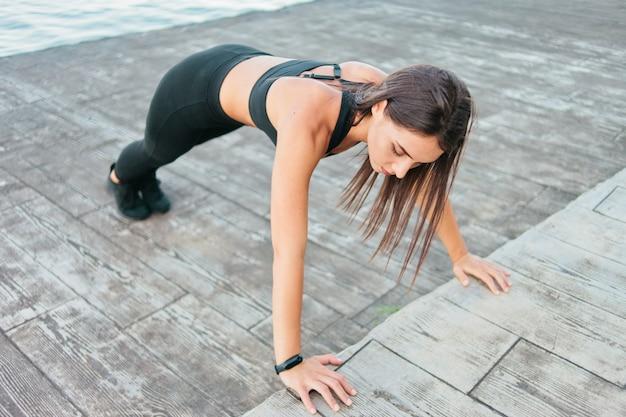 Jovem apta a mulher em roupas esportivas fazendo exercícios de flexão na praia
