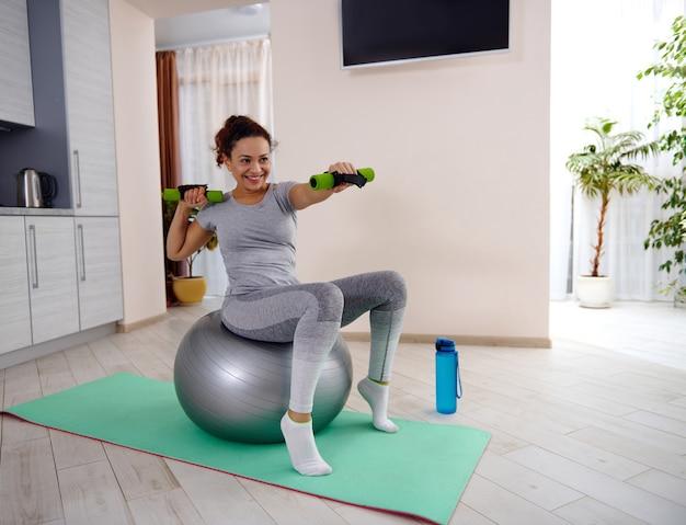 Jovem apta a mulher em roupas esportivas, senta-se em uma bola de fitness e segura halteres enquanto treina. aproveitando o treino em casa