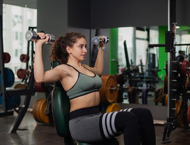 Jovem apta a mulher fazendo exercícios de supino com halteres no ginásio. conceito de estilo de vida saudável. treinamento de peso livre