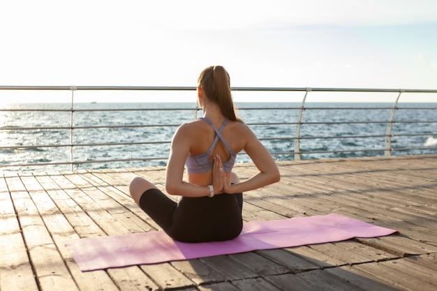 Jovem apta a mulher fazendo hatha ioga na praia pela manhã. meditação ao ar livre
