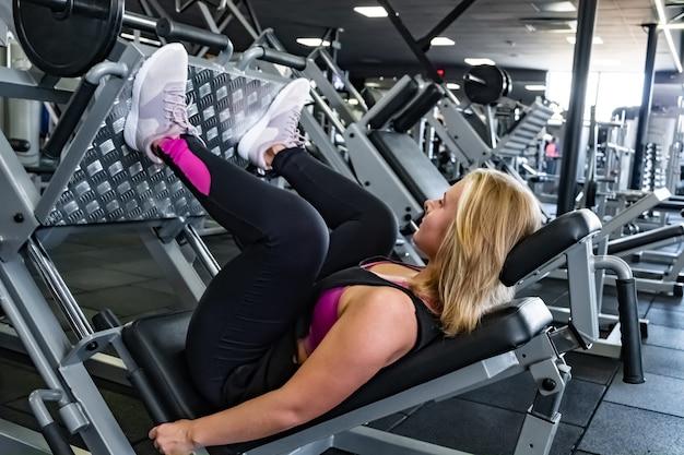 Jovem apta a mulher na academia fazendo exercícios musculares de perna com máquina de leg press. atleta feminina em uma sala de ginástica, malhando com máquina de musculação de perna