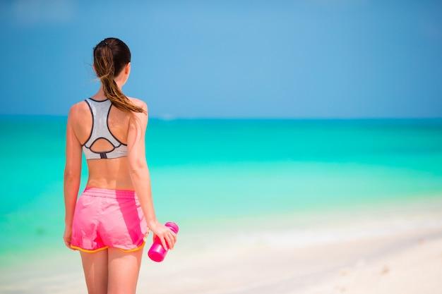 Jovem apta com garrafa de água na praia branca