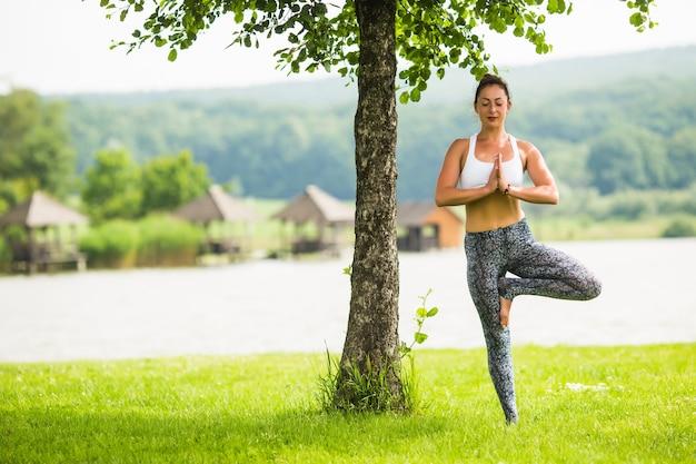 Jovem apta fazendo ioga no parque perto do lago e da árvore