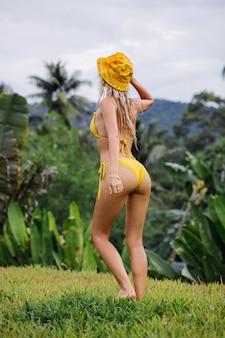 Jovem apta mulher caucasiana com cabelo loiro em biquíni amarelo e o panamá da moda de verão se divertindo em um campo tropical