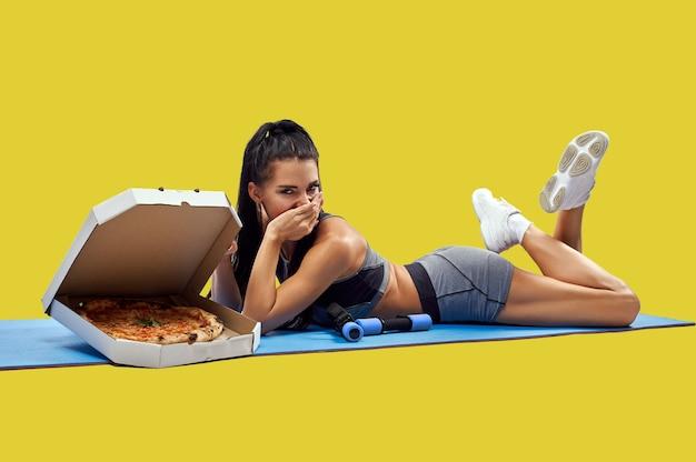 Jovem apta mulher cobre a boca com a mão enquanto está deitado em um tapete de fitness perto de uma caixa com saborosa pizza fresca. isolado. conceito de perder peso e engordar