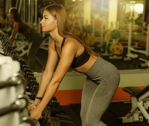 Jovem apta mulher em roupas esportivas pega halteres pesados de um rack no ginásio. conceito de estilo de vida saudável.
