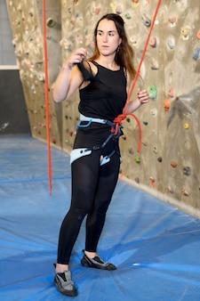 Jovem apta mulher escalando na parede de pedra interna.