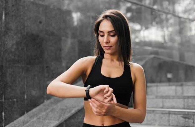 Jovem apta mulher olhando para uma pulseira inteligente em escadas de mármore cinza ao ar livre.