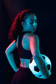 Jovem apta segurando bola de futebol