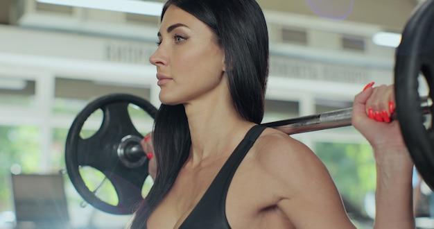 Jovem aptidão linda garota levantando uma cruz de peso fit no ginásio. mulher bonita e desportiva fazendo agachamento com barra, gostando de malhar.