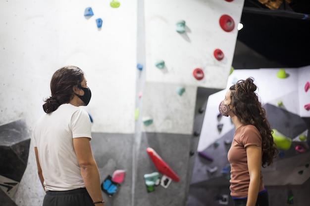Jovem apto alpinistas e homens usando máscara em parede íngreme de pedra dentro de casa