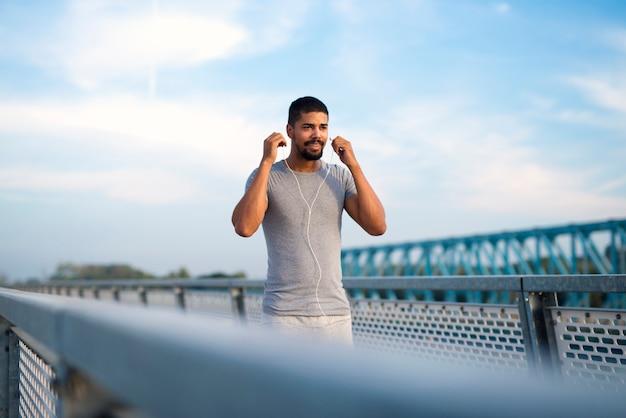 Jovem apto desportista usando fones de ouvido e se concentrando para o treino
