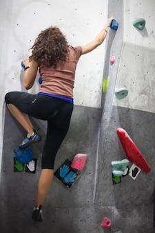 Jovem apto escalador de mulher subindo na parede de rocha, escalando na parede artificial dentro de casa.
