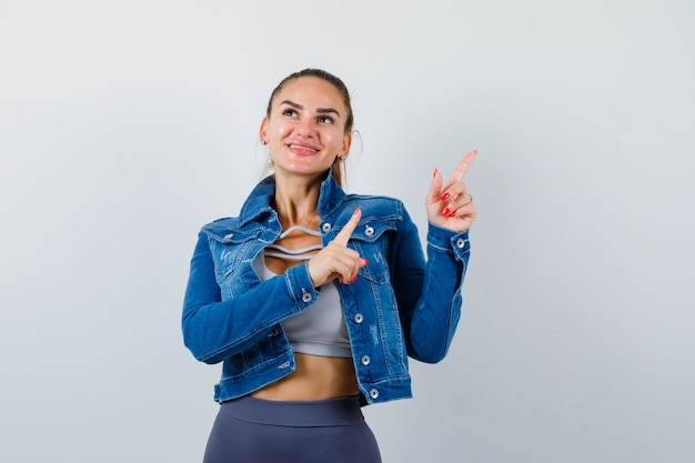 Jovem apto feminino apontando para o canto superior direito enquanto olha para longe na parte superior, jaqueta jeans e olhando alegre, vista frontal.