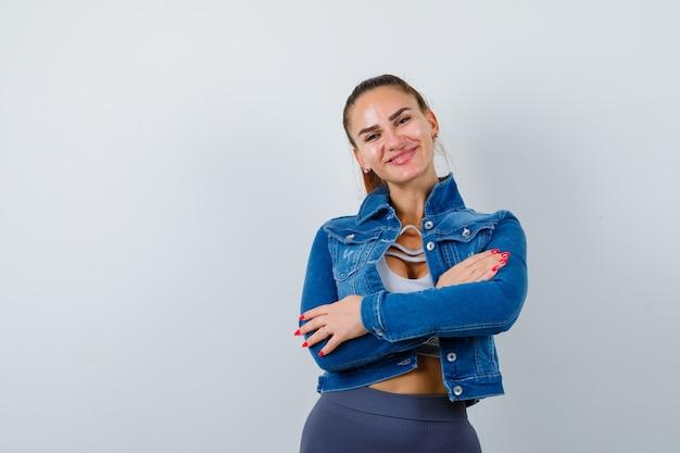 Jovem apto feminino com os braços cruzados na parte superior, jaqueta jeans e olhando alegre, vista frontal.