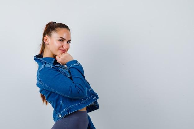 Jovem apto feminino no top, jaqueta jeans apoiando o queixo no punho enquanto posava e olhando alegre, vista frontal.