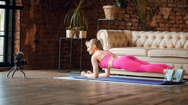 Jovem apto garota blogueira fazendo tapete de prancha com roupa esportiva com câmera fazendo exercícios online em casa, gravando tutoriais aeróbicos online em casa, exercício na câmera