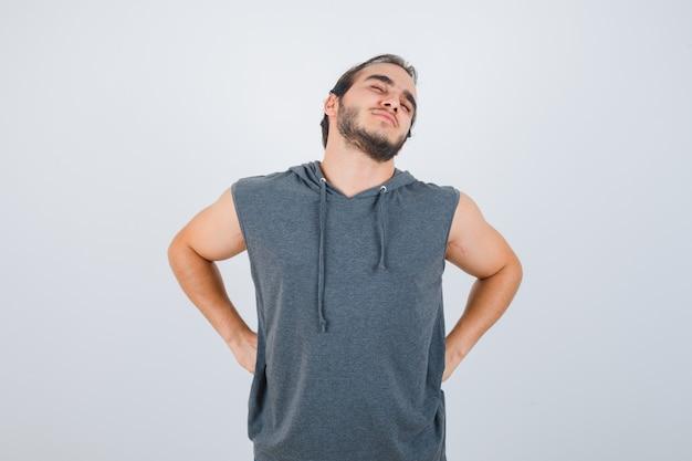 Jovem apto homem com capuz sem mangas, sofrendo de dores nas costas e parecendo indisposto, vista frontal.