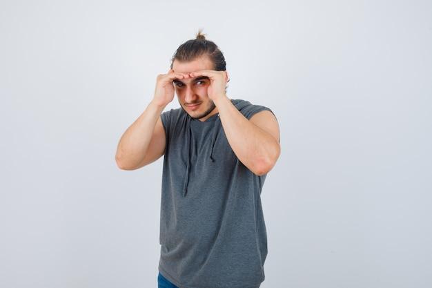 Jovem apto homem segurando as mãos na cabeça para ver claramente no moletom sem mangas e olhar focado, vista frontal.