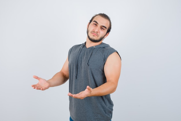 Jovem apto masculino com capuz sem mangas, mostrando um gesto de impotência e parecendo chateado, vista frontal.