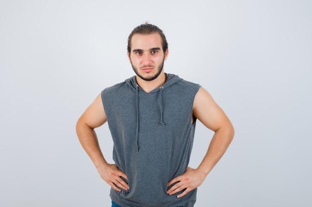 Jovem apto masculino com capuz sem mangas, posando com as mãos na cintura e parecendo confiante, vista frontal.