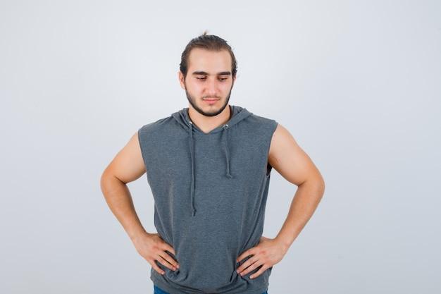 Jovem apto masculino com capuz sem mangas, posando com as mãos na cintura e parecendo pensativo, vista frontal.