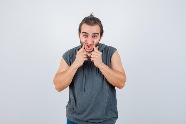 Jovem apto masculino com capuz sem mangas pressionando as bochechas com os dedos e parecendo feliz, vista frontal.