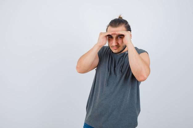 Jovem apto masculino com capuz sem mangas, segurando as mãos na cabeça para ver claramente e olhar focado, vista frontal.