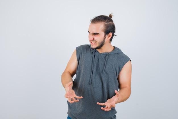 Jovem apto masculino em um moletom sem mangas, mantendo as mãos de maneira agressiva e parecendo irritado, vista frontal.