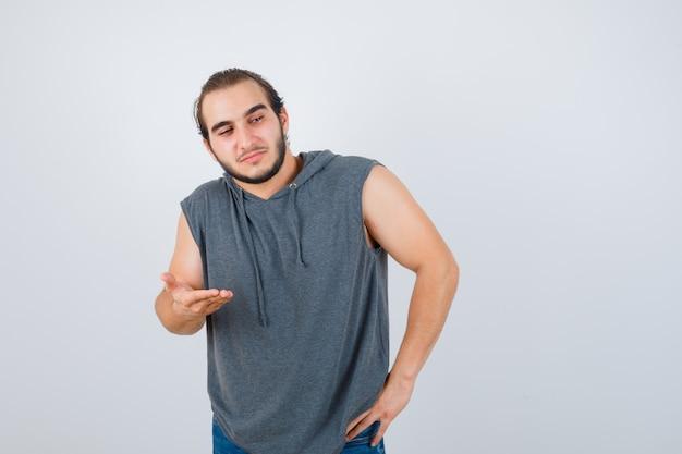 Jovem apto masculino espalhando palma com capuz sem mangas e parecendo confiante. vista frontal.