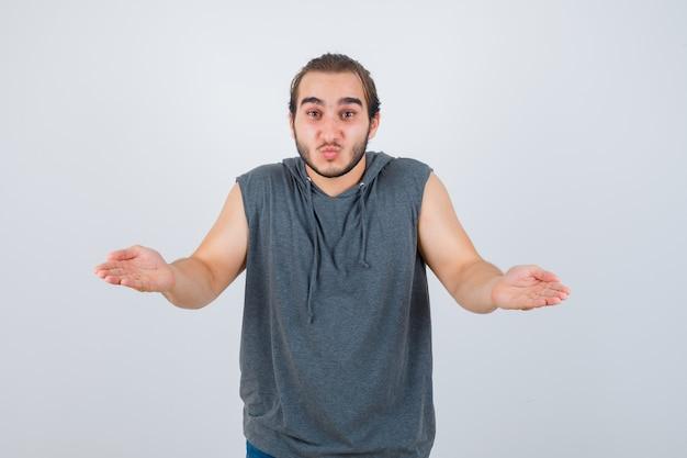 Jovem apto masculino fingindo segurar algo em um moletom sem mangas e parecendo hesitante. vista frontal.
