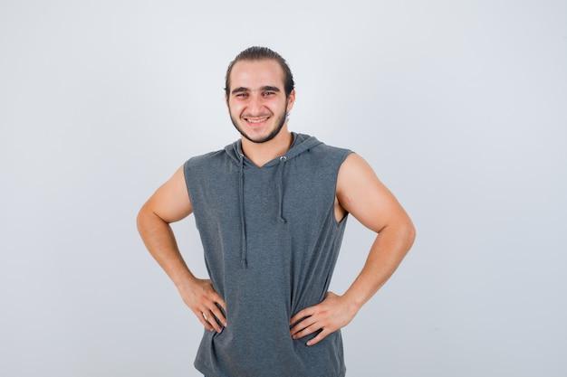 Jovem apto masculino posando com as mãos na cintura em um capuz sem mangas e olhando alegre, vista frontal.