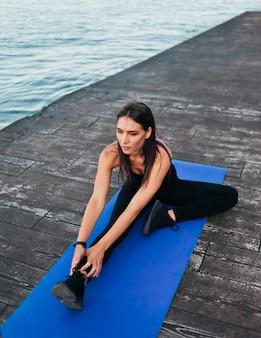 Jovem apto mulher com roupas de esporte, fazendo exercícios de alongamento de pernas na esteira de ioga na praia.