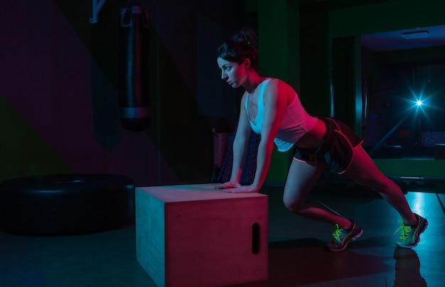 Jovem apto mulher flexões de uma caixa de madeira em néon gradiente vermelho azul luz em uma parede escura conceito de treinamento funcional.
