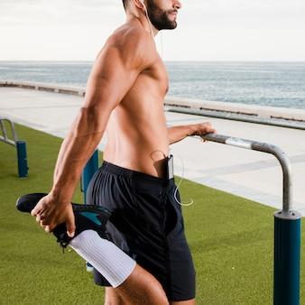 Jovem aquece antes de exercitar