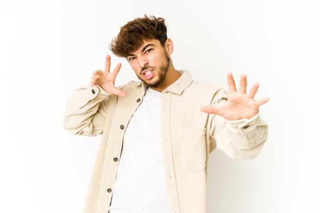 Jovem árabe chateado em branco, gritando com as mãos tensas.