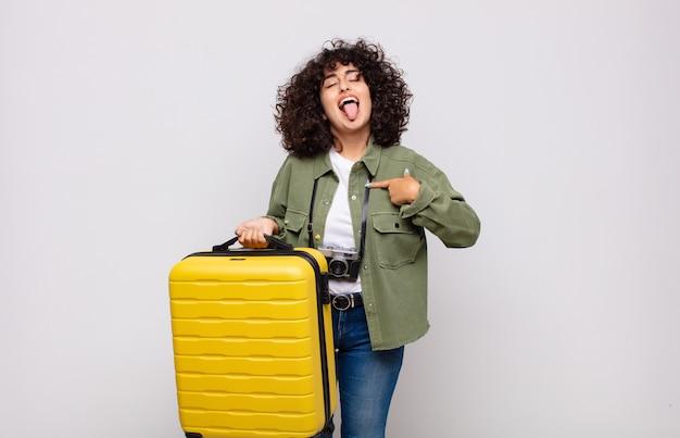 Jovem árabe com atitude alegre, despreocupada e rebelde, brincando e mostrando a língua, se divertindo o conceito de viagens