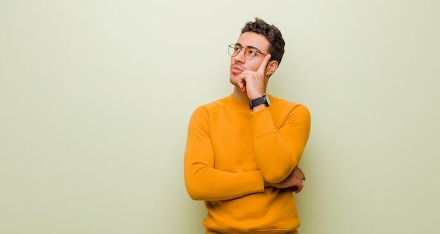 Jovem árabe com um olhar concentrado, pensando com uma expressão duvidosa, olhando para cima e para o lado contra a parede plana
